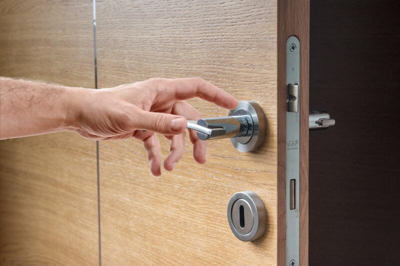 Ręka mężczyzny otwierająca drzwi