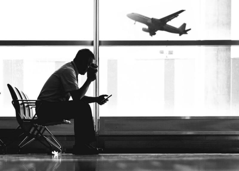 Mężczyzna siedzi na lotnisku z telefonem w ręce, w tle widać samolot